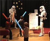 Stormtroopers pose with kids playing with lightsabers