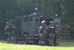 Tactical team gets back into back of an armor plated vehicle