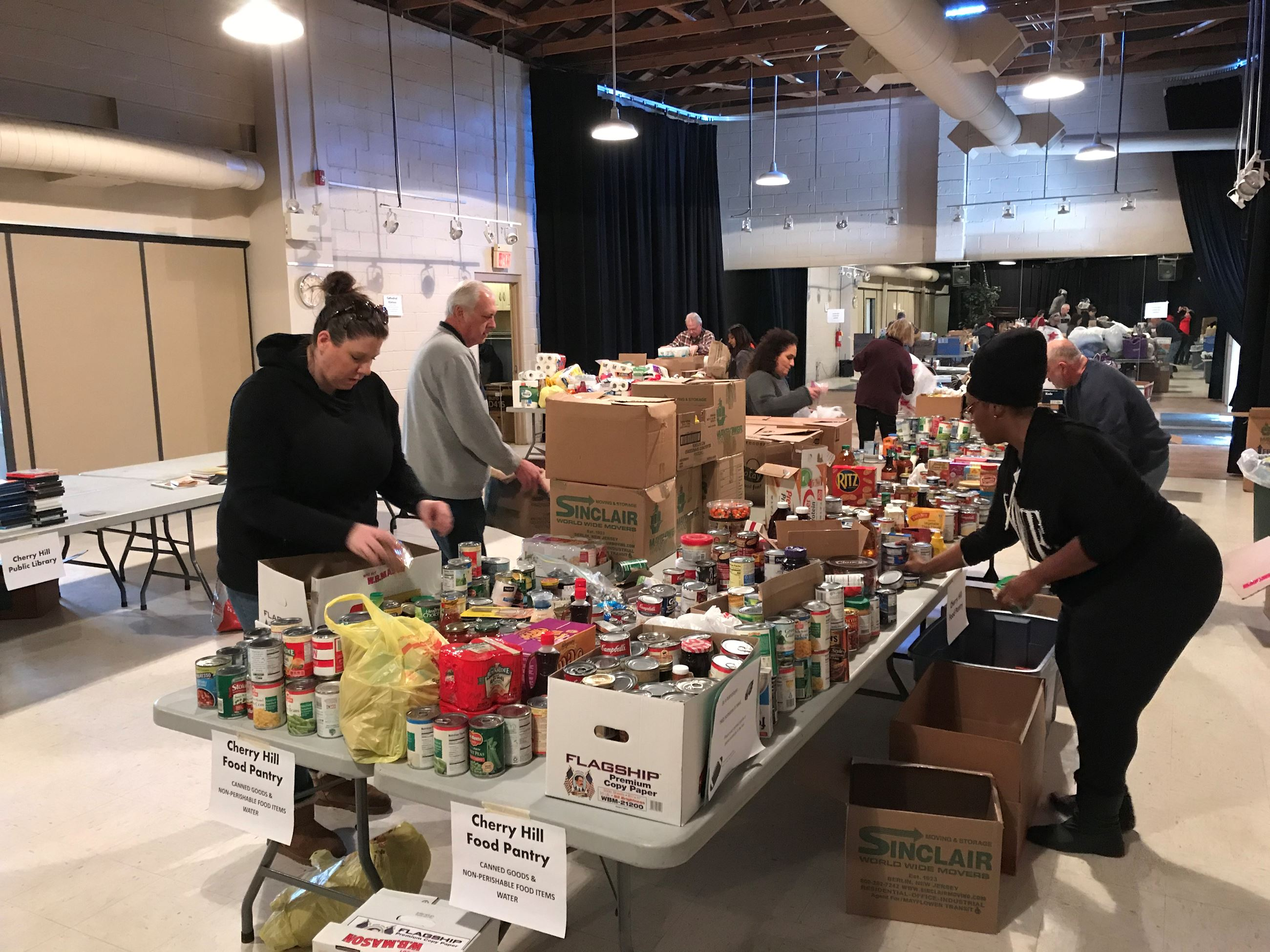Volunteers at table laden with donations for food pantry