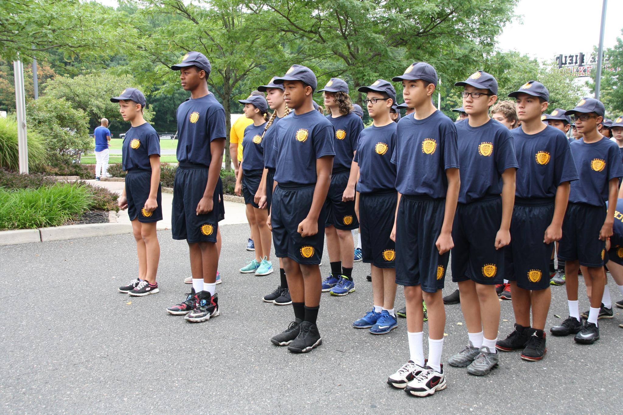 Youth in navy uniforms standing at attention