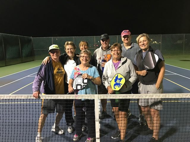 Eight adults behind tennis net at night